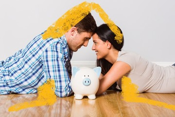 Young couple lying on floor smiling with piggy bank