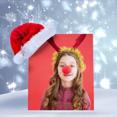 Composite image of festive little girl wearing red nose