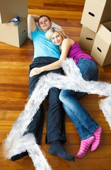 Composite image of cute couple sleeping on the floor