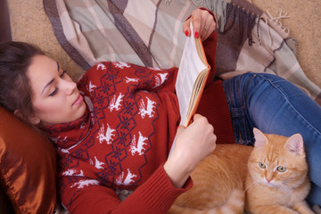 Girl lying on the sofa with red cat and reading a book