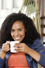 Beautiful black woman drinks on hammock, and smile