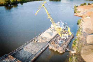 Floating jib crane during loading of sand on barge