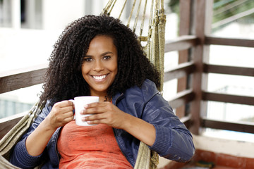 Beautiful black woman drinks on hammock, and smile