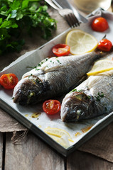 Cooked fish with parsley, tomato and lemon
