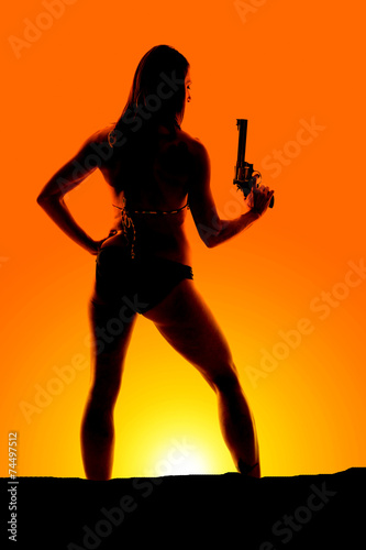 Leinwanddruck Bild silhouette of woman in bikini gun up