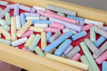 Multicoloured chalk in wood tray