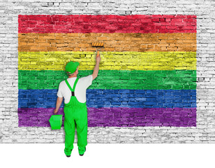House painter covers brick wall with rainbow flag