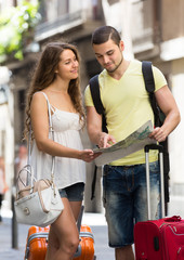 Couple with luggage reading map