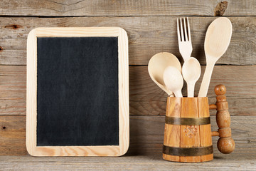 Blank blackboard and wooden spoons and fork in mug