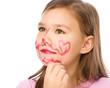 Little girl is applying lipstick on her cheek