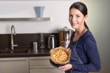 Junge Frau präsentiert ihren selbstgemachten Kuchen