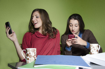 Two girls browsing internet via smart phones, while studying.