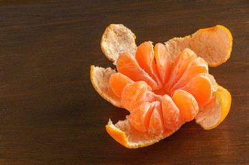Peeled mandarin orange on the wooden background
