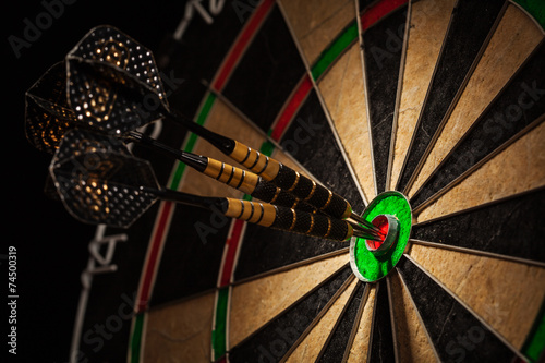 Leinwanddruck Bild Three darts in bull's eye close up