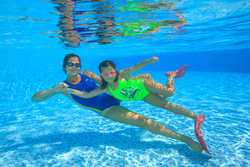 Mother and daughter dive in the swimming pool