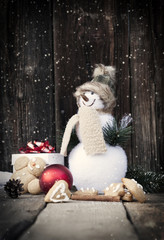 Snowman and Christmas decorations on vintage wooden table