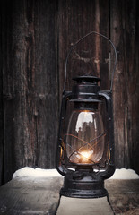 Old oil lamp on vintage wooden table at night