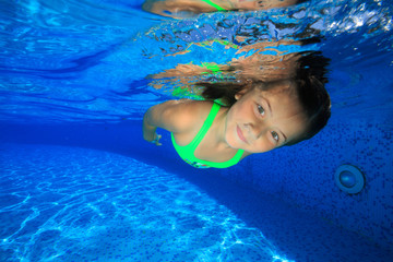 Girl dives into the swimming pool