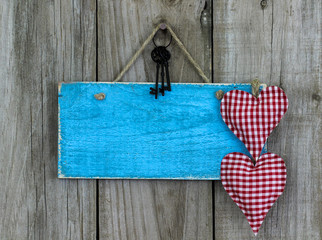 Blank antique blue sign with red hearts on wooden background