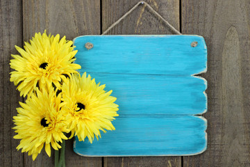 Blank antique blue sign with yellow flowers hanging on door