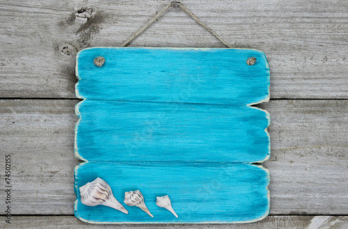 Blank blue sign with seashells hanging on door - 74502155