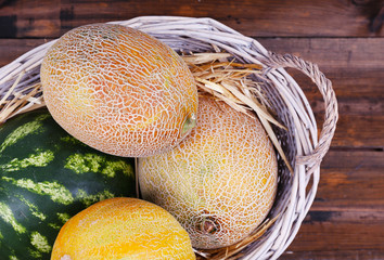 Melons and watermelon in oval wicker basket on wooden