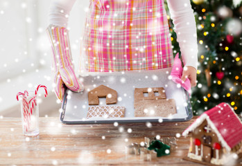 closeup of woman with gingerbread house on pan