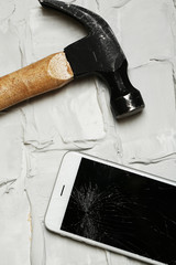 Broken iPhone with hammer on brick background