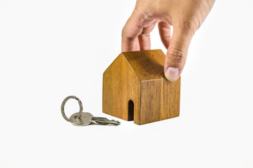 hand try to pick up wodden house model with key