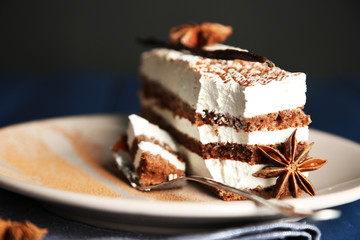 Tasty tiramisu cake on plate, on black background
