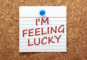 The phrase I'm Feeling Lucky on a card pinned to a cork board