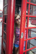 People in London- woman by red phone booth.