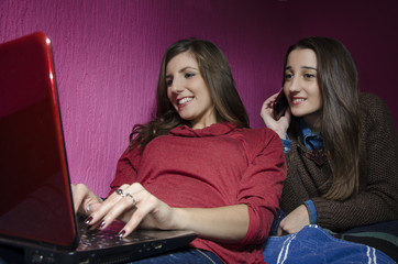 Sisters relaxing at home,one using laptop,other one smartphone