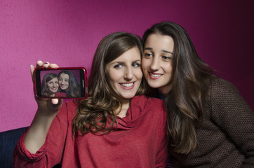 Two beautiful sisters taking a selfie with smart phone