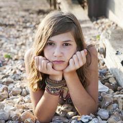 pensive girl lying on the beach