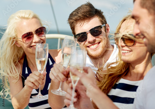 canvas print picture smiling friends with glasses of champagne on yacht