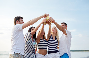 smiling friends clinking bottles on beach