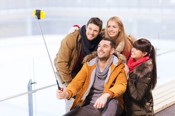 happy friends with smartphone on skating rink