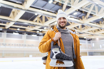 happy young man with ice-skates on skating rink