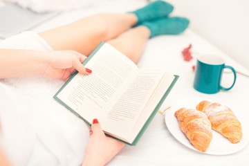 woman reading in bed with croissant as breakfast