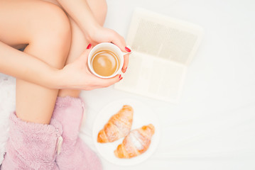 close-up of woman legs with fluffy slippers drinking a coffee