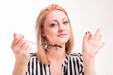 Joyful woman eating insects with a fork in a restaurant