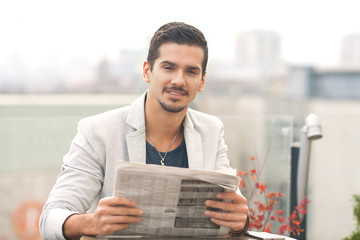 A young businessman reading a newspaper outdoors
