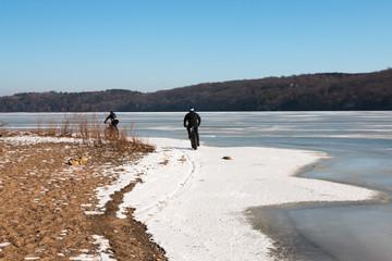 Men riding fat-bikes along frozen Mississippi River