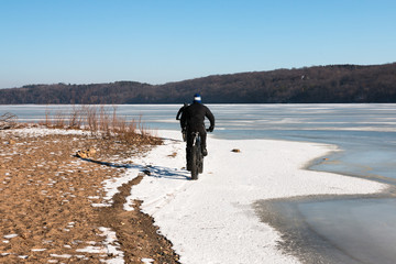 Two men on fat-bikes ride on a shore of frozen Mississippi River