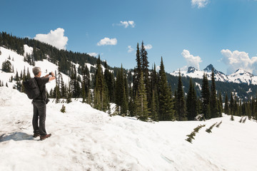 Man in summer clothes stand on snow and takes pictures of mounta