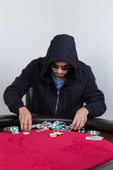 Poker player rakes in chips and starts to stack them