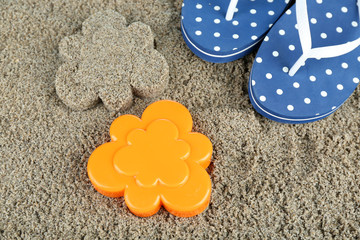 Plastic flower-shaped mold and flip flops on  sand, close-up