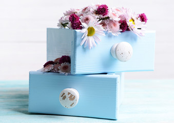 Beautiful flowers in boxes on table on light background