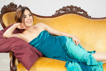 woman in teal dress, reclining with a smile